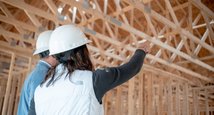 Two People Looking At A New Home Structure