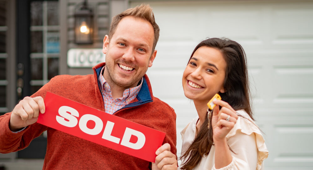 Couple holding the key and sold banner in front of their new home from Rolwes Company.