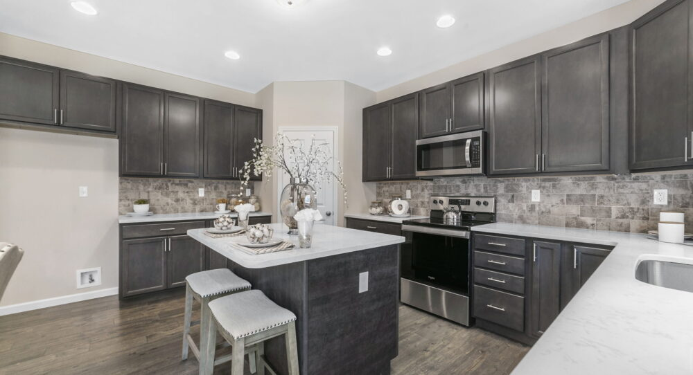 Kitchen with island set for two in a new home from Rolwes Co.